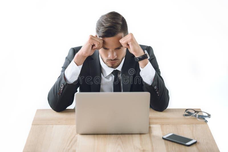 Ritratto dell'uomo d'affari stanco che si siede nel luogo di lavoro con il computer portatile e lo smartphone fotografia stock