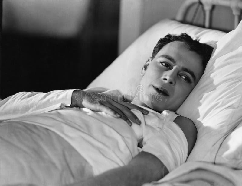 Ritratto dell'uomo danneggiato a letto immagine stock