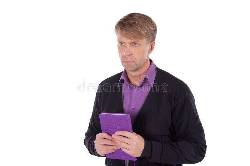 Ritratto dell'uomo di medio evo vestito in cardigan con un taccuino su fondo bianco fotografia stock libera da diritti