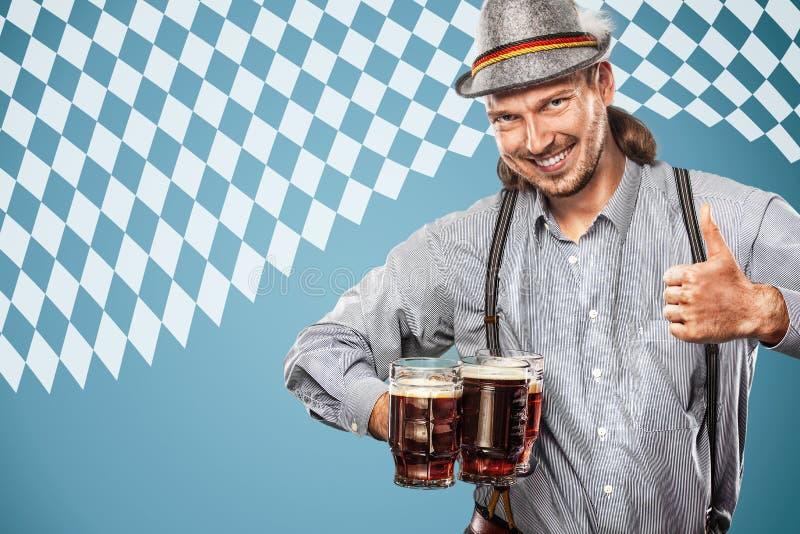 Ritratto dell'uomo di Oktoberfest, durare vestiti bavaresi tradizionali, grandi tazze di birra serventi fotografia stock libera da diritti