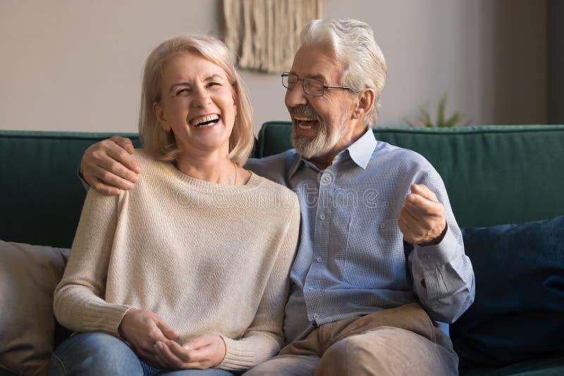 Ritratto dell'uomo e della donna di risata invecchiati mezzo a casa fotografie stock