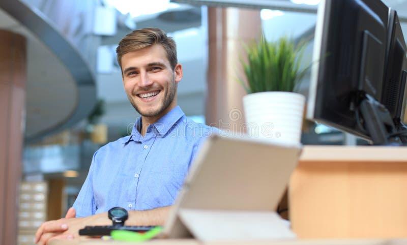 Ritratto dell'uomo felice che si siede alla scrivania, esaminando macchina fotografica, sorridente fotografia stock