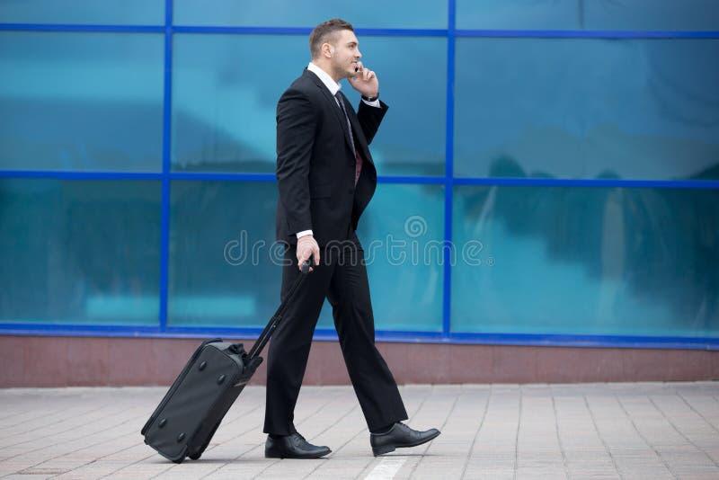 Ritratto dell'uomo felice di affari che cammina con la valigia in un viaggio fotografia stock libera da diritti