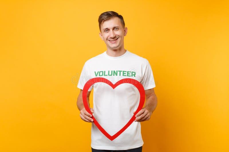 Ritratto dell'uomo felice in maglietta bianca con il titolo scritto di verde dell'iscrizione tenuta volontaria grande cuore di le fotografia stock