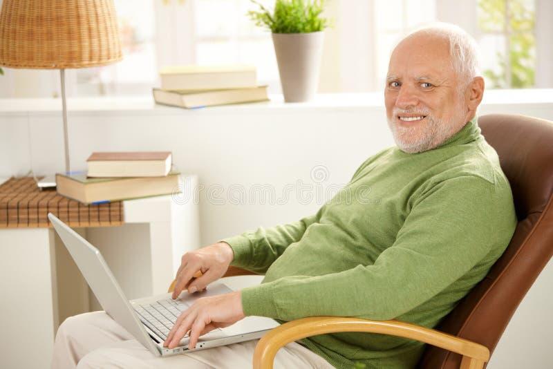 Ritratto dell'uomo invecchiato con il computer portatile immagine stock