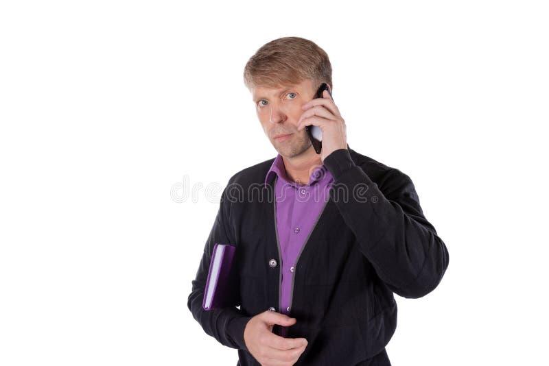 Ritratto dell'uomo invecchiato medio che tiene un taccuino e che parla sul telefono cellulare sopra fondo bianco immagine stock libera da diritti