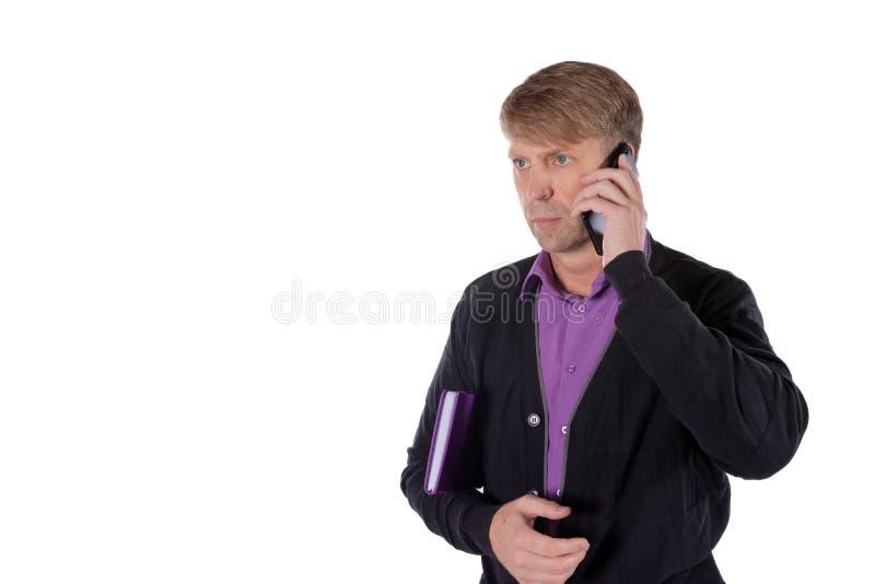 Ritratto dell'uomo invecchiato medio che tiene un taccuino e che parla sul telefono cellulare sopra fondo bianco fotografia stock