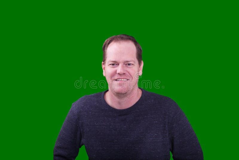 Ritratto dell'uomo invecchiato medio dai capelli rossi che sorride sul fondo di schermo verde immagini stock libere da diritti
