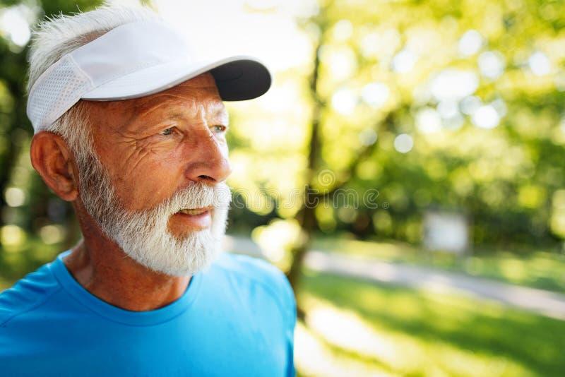 Ritratto dell'uomo maturo atletico dopo il funzionamento Uomo senior bello che riposa dopo il trotto al parco immagini stock libere da diritti
