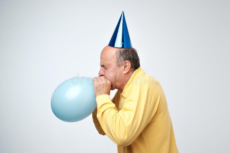 Ritratto dell'uomo maturo in maglietta gialla e cappuccio divertente che soffiano un pallone blu sopra un fondo bianco immagine stock