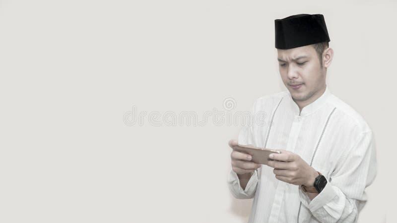 Ritratto dell'uomo musulmano asiatico bello con il cappuccio capo e per mezzo dello smartphone e seriamente il gioco del video gi fotografie stock libere da diritti