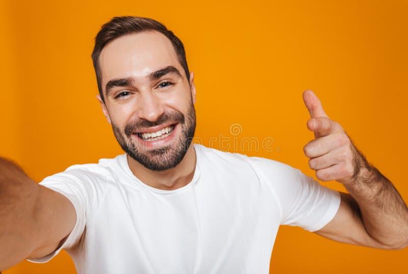 Ritratto dell'uomo ottimista 30s in maglietta che ride mentre prendendo la foto del selfie, isolato sopra fondo giallo immagine stock