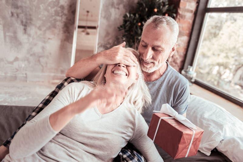 Ritratto dell'uomo positivo con la sorpresa per la sua moglie fotografia stock