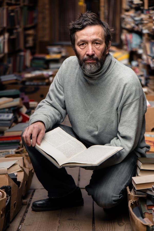 Ritratto dell'uomo senior autentico sul mercato del libro immagini stock