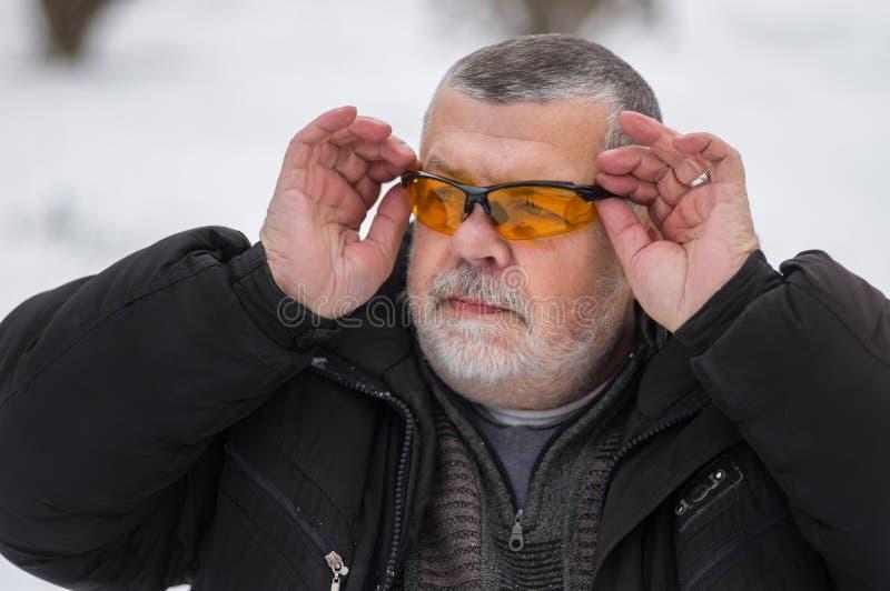 Ritratto dell'uomo senior caucasico barbuto che regola i vetri di sole alla stagione invernale fotografie stock libere da diritti