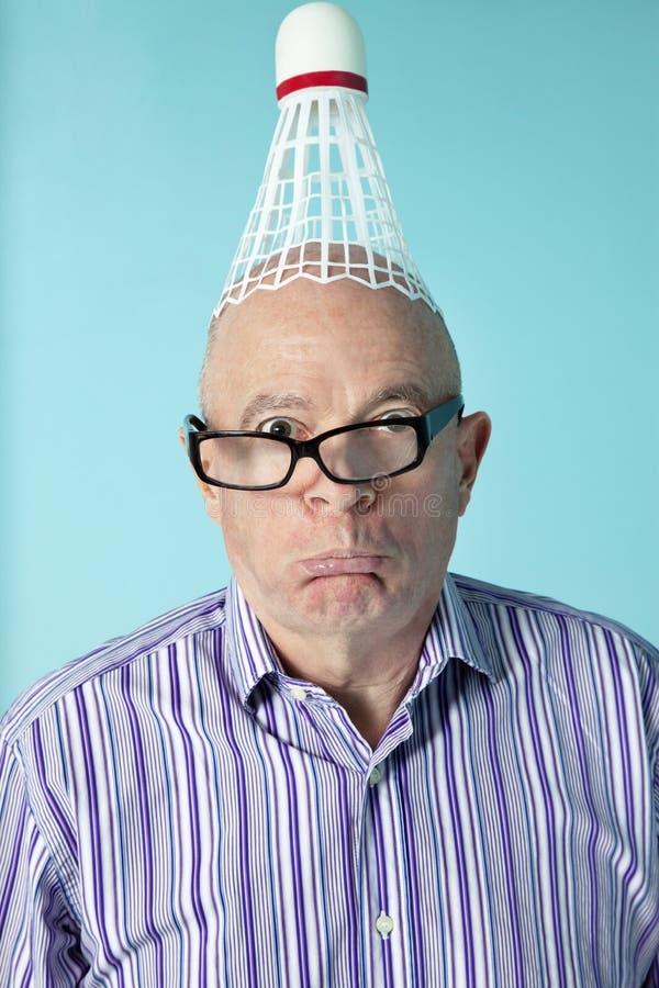 Ritratto dell'uomo senior che fa fronte con il volano sulla testa immagini stock libere da diritti