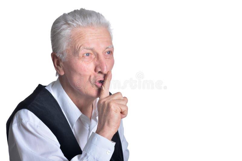 Ritratto dell'uomo senior con il gesto di silenzio su fondo bianco immagini stock