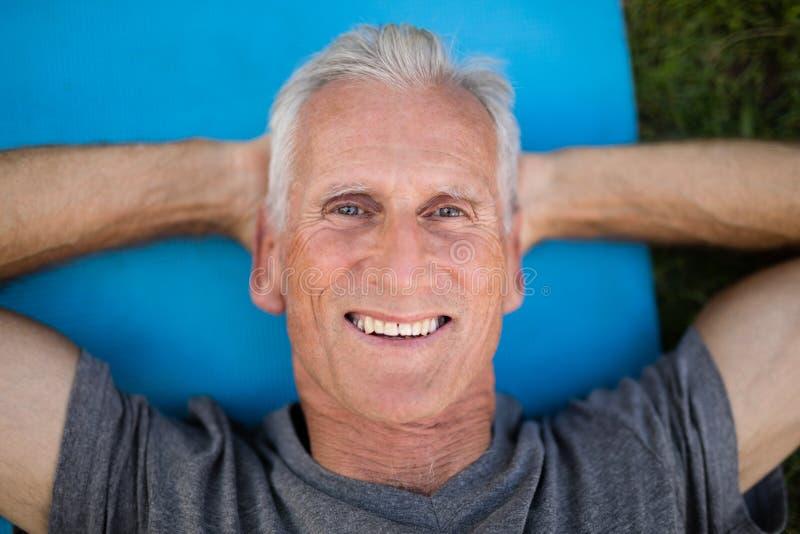 Ritratto dell'uomo senior sorridente che si trova sulla stuoia di esercizio fotografie stock