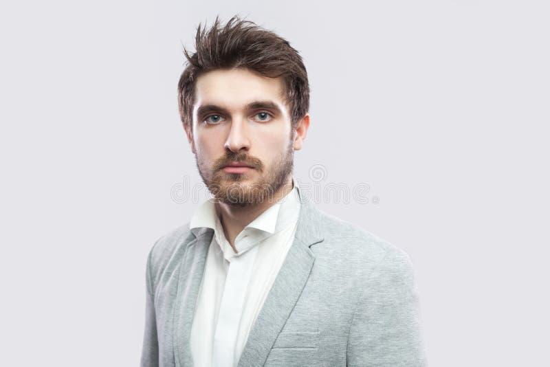 Ritratto dell'uomo serio barbuto bello con i capelli marroni e della barba in camicia bianca e nella condizione grigia casuale de immagini stock