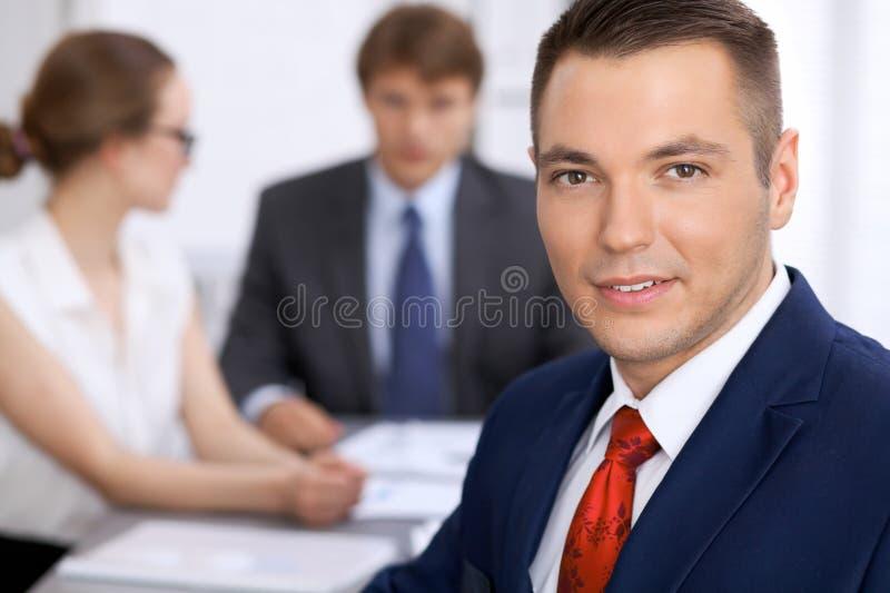 Ritratto dell'uomo sorridente allegro di affari contro un gruppo di gente di affari ad una riunione immagine stock libera da diritti