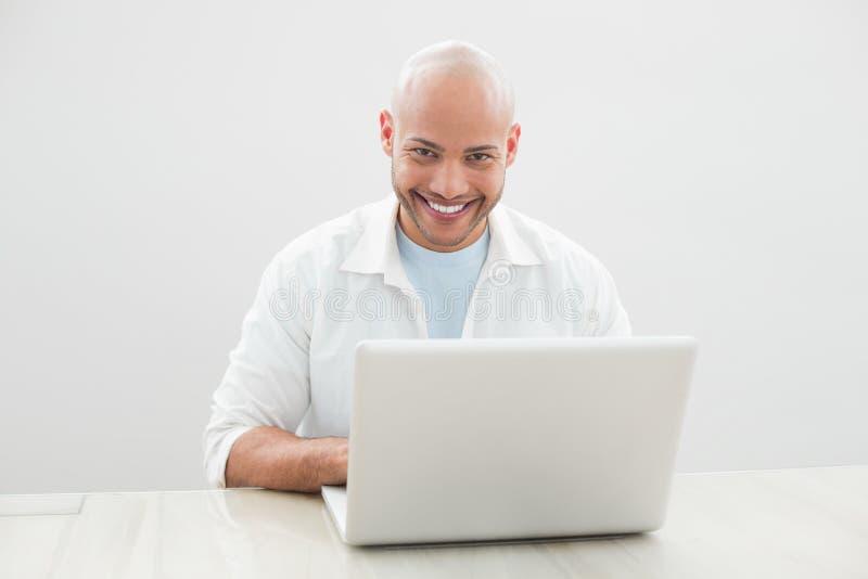 Ritratto dell'uomo sorridente casuale che per mezzo del computer portatile allo scrittorio immagini stock