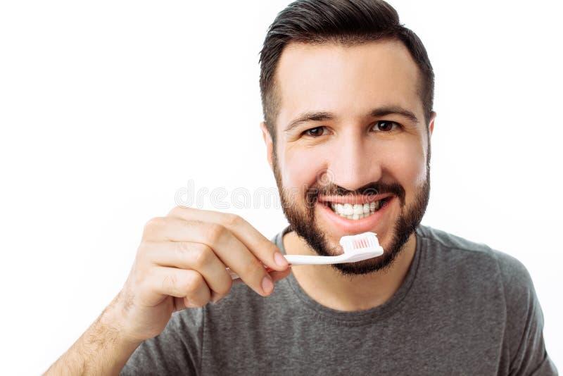 Ritratto dell'uomo sorridente con la barba, con lo spazzolino da denti, sull'isolato su fotografie stock