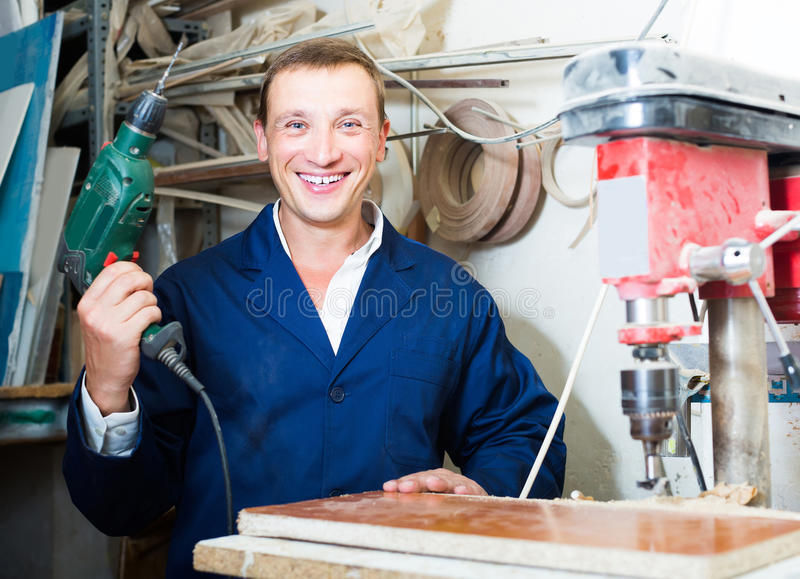 Ritratto dell'uomo in uniforme che funziona con il cacciavite elettrico o immagine stock