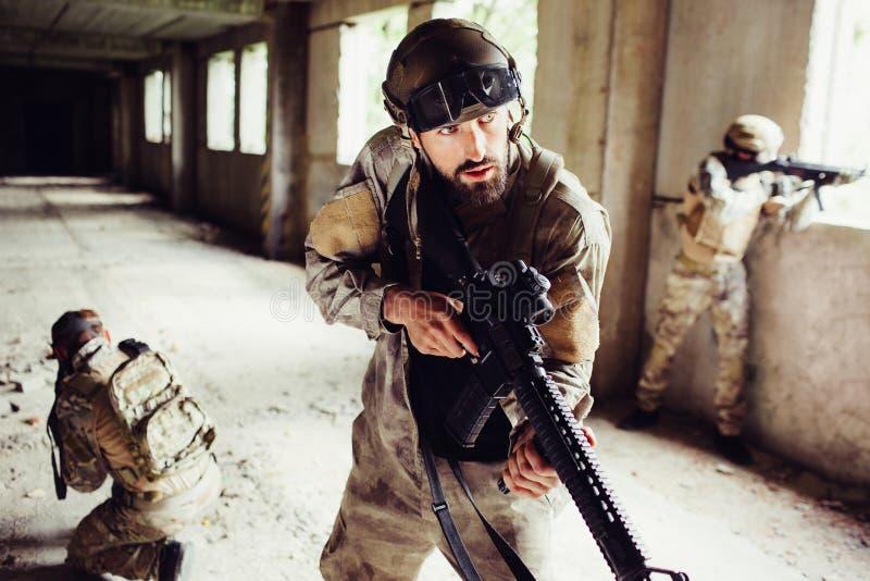 Ritratto dell'uomo in uniforme che sta nella stanza vuota con gli altri soldati ed attesa Stanno molto attenti I tipi sono dentro immagini stock