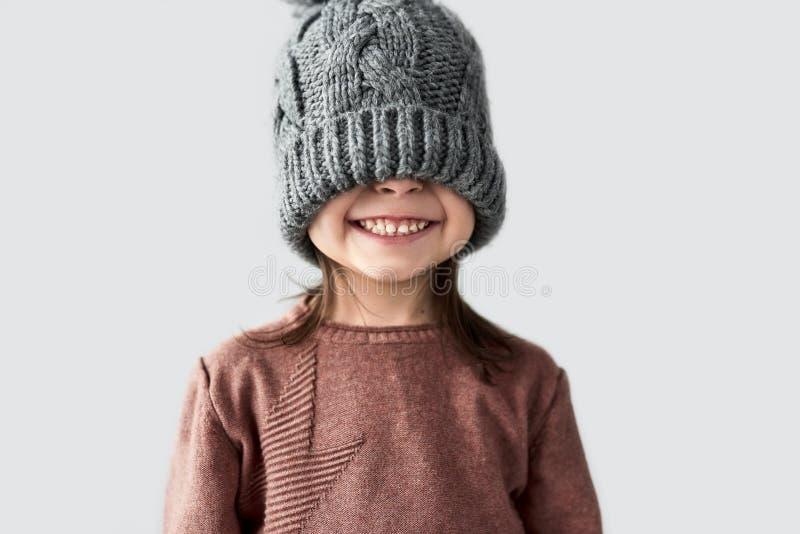 Ritratto della bambina allegra divertente nascosta gli occhi in cappello grigio caldo di inverno, maglione sorridente e d'uso all fotografia stock