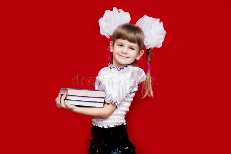 Ritratto della bambina allegra in vetri molto grandi isolati su rosso Concetto di vista o di insegnamento immagini stock libere da diritti