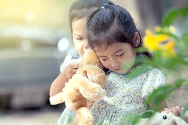 Ritratto della bambina asiatica sveglia che gioca con la sua bambola immagini stock