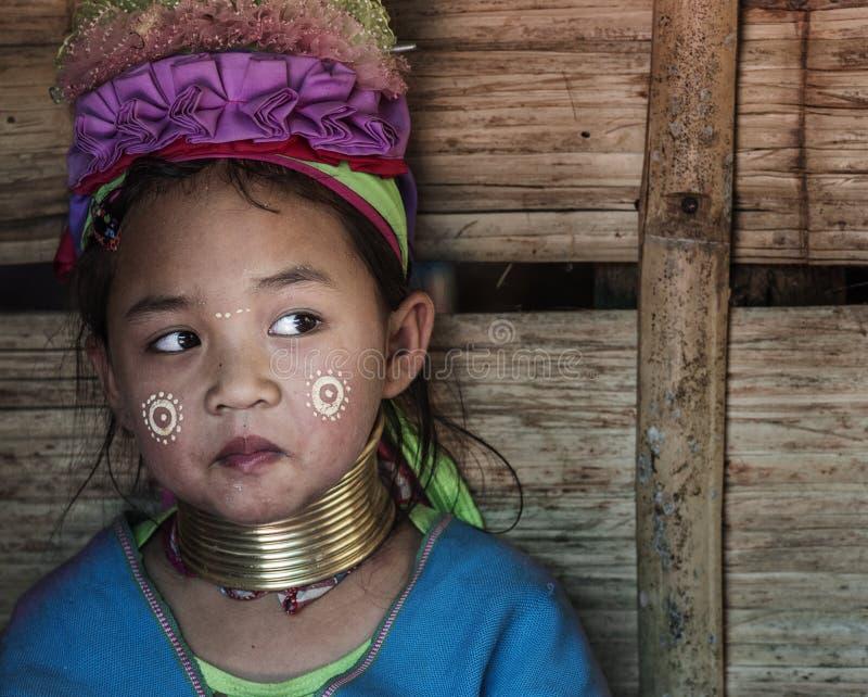 Ritratto della bambina che appartiene alla comunità lunga della tribù del collo che si siede fuori della sua casa nel villaggio l fotografie stock