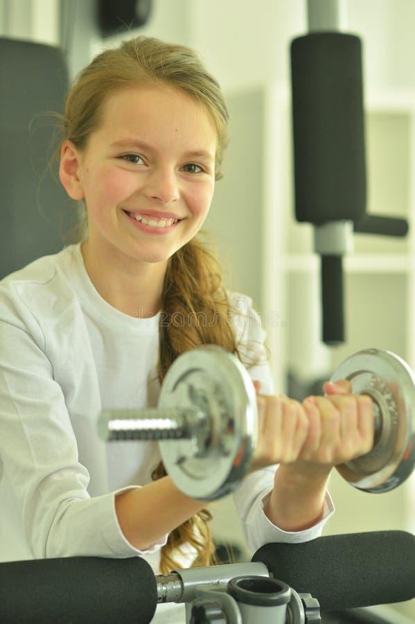 Ritratto della bambina che fa gli esercizi con la testa di legno in palestra immagine stock