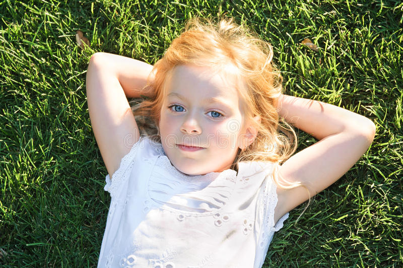 Ritratto della bambina che si distende sull'erba verde immagine stock