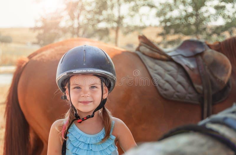 Ritratto della bambina e del cavallo marrone Ragazza con i caschi immagine stock libera da diritti