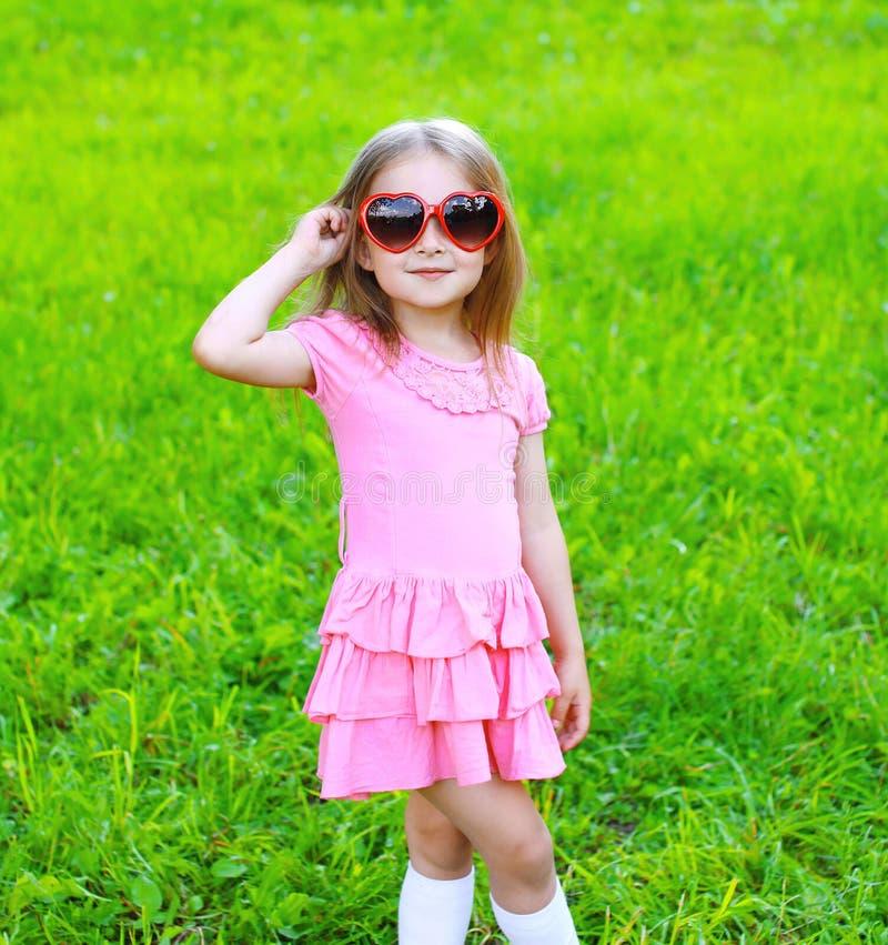 Ritratto della bambina in occhiali da sole sull'erba fotografia stock libera da diritti