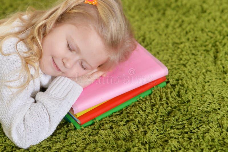 Ritratto della bambina sveglia che dorme sul mucchio dei libri fotografie stock