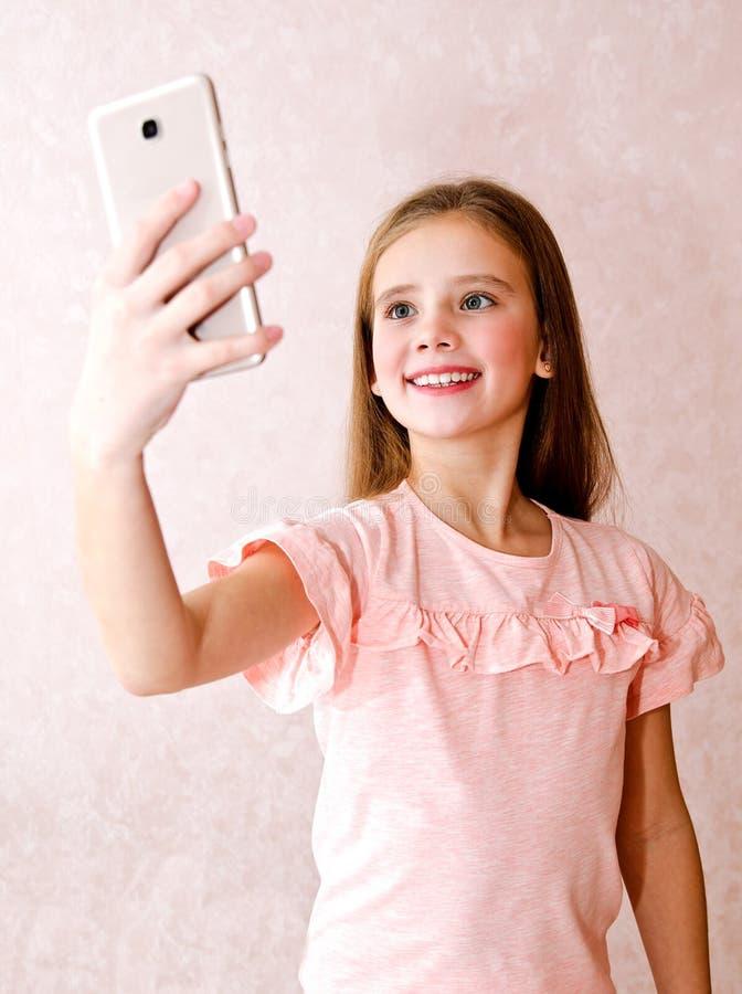 Ritratto della bambina sveglia che prende un selfie isolato fotografia stock libera da diritti