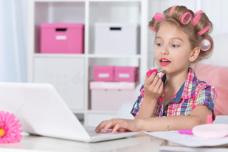 Ritratto della bambina sveglia che si siede alla tavola con il computer portatile immagine stock