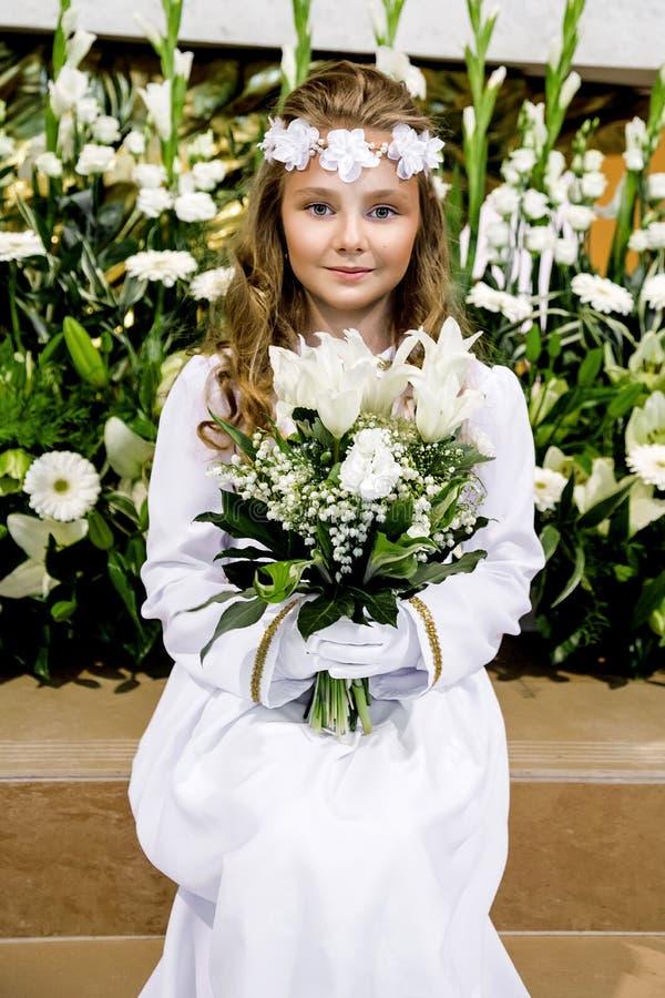 Ritratto della bambina sveglia sul vestito e sulla corona bianchi sul primo portone della chiesa del fondo di comunione santa immagine stock libera da diritti