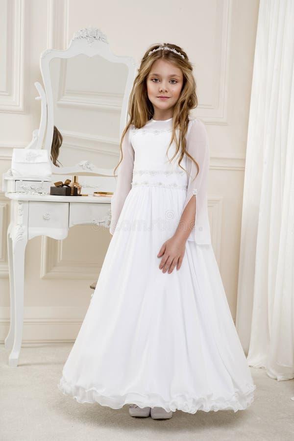 Ritratto della bambina sveglia sul vestito e sulla corona bianchi sul primo portone della chiesa del fondo di comunione santa fotografia stock