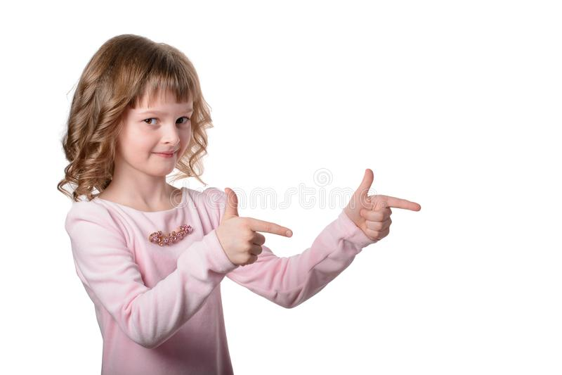 Ritratto della bambina in vestito rosa che indica le dita il lato allo spazio vuoto della copia Ragazza sorridente stante isolata fotografie stock