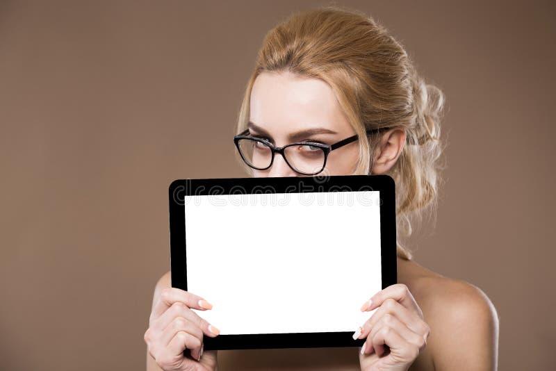 Ritratto della bionda in vetri con una compressa in mani immagine stock