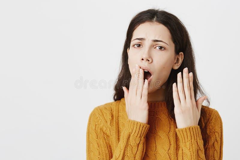 Ritratto della bocca adulta femminile sveglia annoiata e stanca della copertura mentre sbadigliando e gesturing con un altro, agg immagine stock