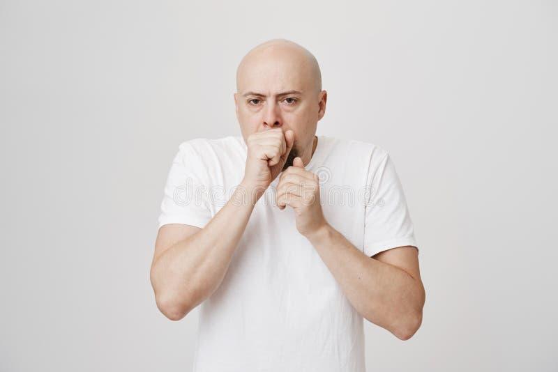Ritratto della bocca vicina dell'uomo del pugno caucasico barbuto calvo infelice della tenuta come se volendo gettare su o tossen fotografia stock