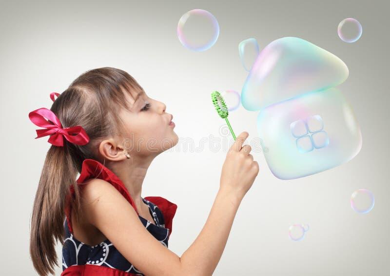 Ritratto della bolla di sapone di salto della ragazza del bambino che forma casa, habita immagine stock libera da diritti