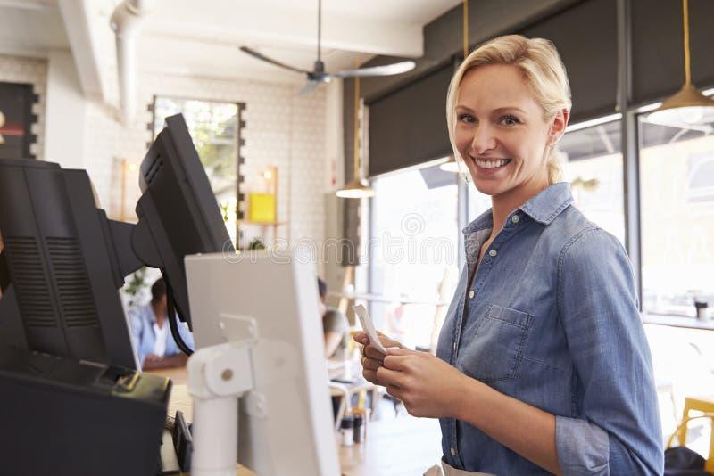 Ritratto della cameriera di bar At Cash Register in caffetteria fotografie stock