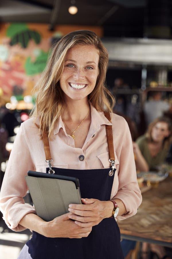 Ritratto della cameriera di bar Holding Menus Serving nel ristorante occupato di Antivari immagine stock