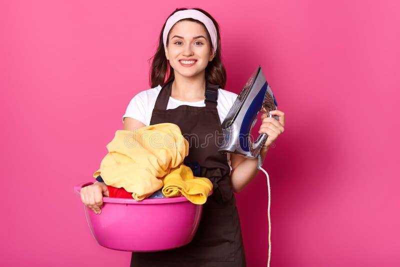 Ritratto della casalinga sincera allegra che esamina direttamente la macchina fotografica, il grembiule marrone d'uso, la fascia  fotografia stock libera da diritti