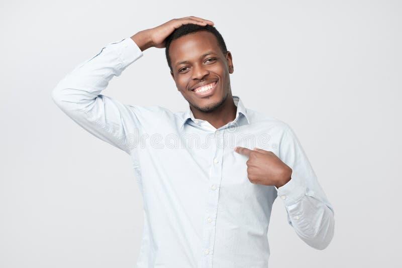 Ritratto della condizione africana bella fiera dell'uomo, esaminante macchina fotografica ed indicantesi immagine stock